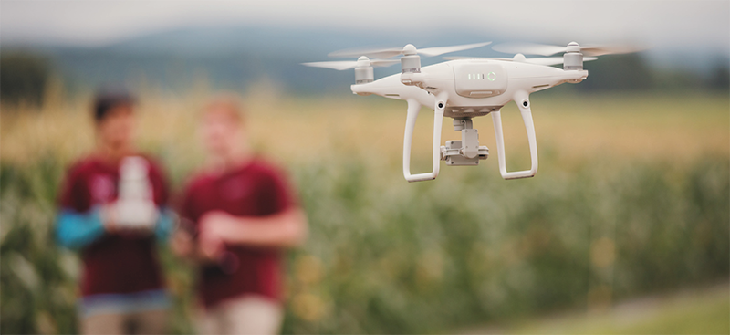 Image of two students flying a drone over a field